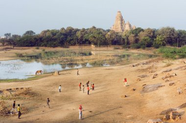 Landscape with Hindu temple of Khajuraho and children playing cricket, India