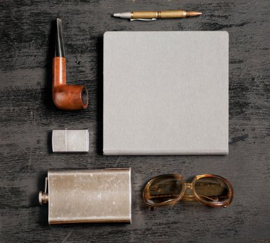 Gentlemanly set: flask for whiskey, lighter, sun glasses, notebook, pen and smoking pipe.