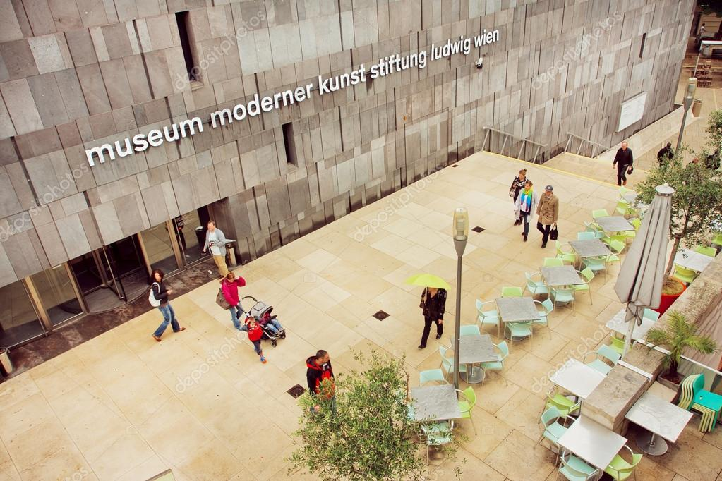 People Walking Around Museum Of Modern Art With Outdoor Cafe