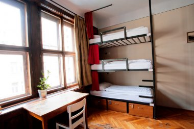 Three-level dormitory beds inside the hostel room for six tourists or the students
