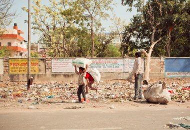 Poor children collect rubbish on the streets for recycling