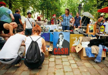 Young people choosing books, draws, portrait of Johnny Cash on street market