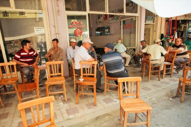 Senior men sitting around tables and talking in rustic cafe of village