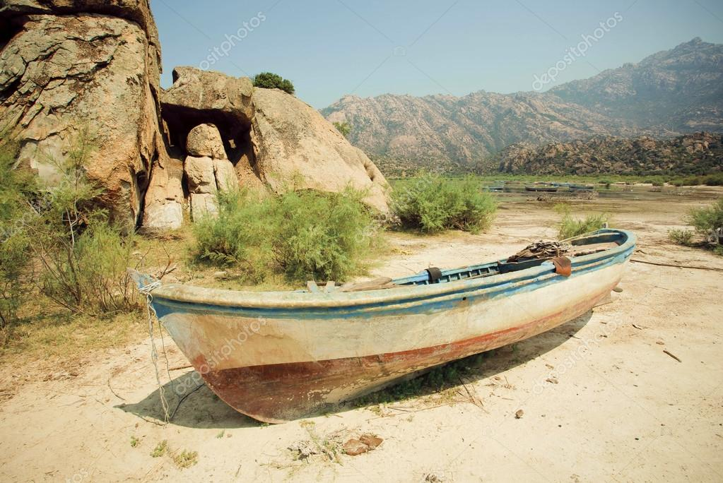 Rural landscape with old fishing boat on the dry land of beach,  lake Bafa, rural Turkey.