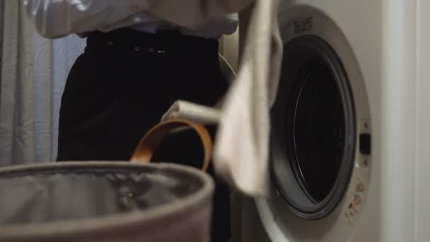 Egy nő ruhákat pakol a mosógépbe.