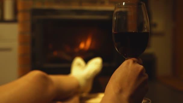Frau mit Glas Rotwein ruht am Kamin.