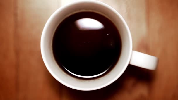 Drop of freshly brewed coffee falling into the cup. Slow motion video.