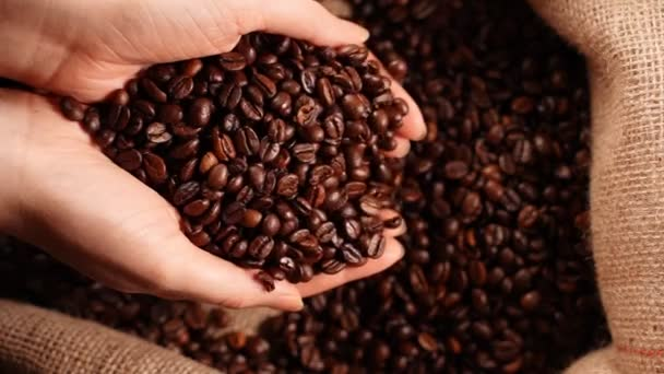 Coffee beans falling from womens hands.