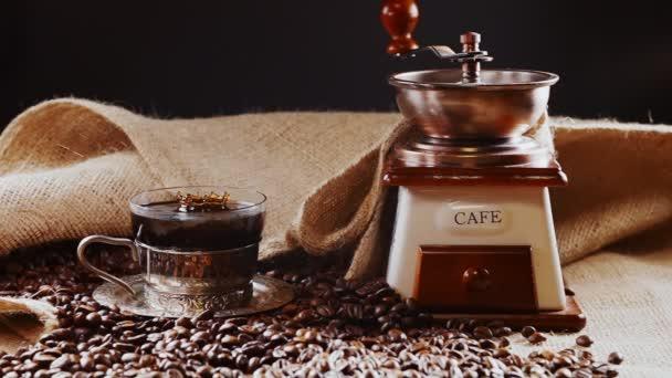 Kapka turecké kávy padající do skleněného kelímku.