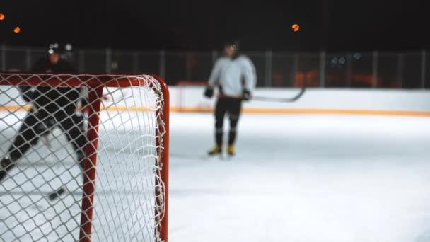 Lidé hrají hokej venku v zimním období.