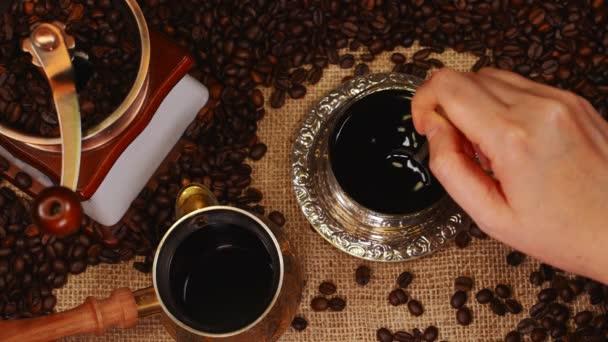 Nő kéz keverés kávé csészében.