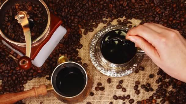 Žena ruka míchání kávy v šálku.