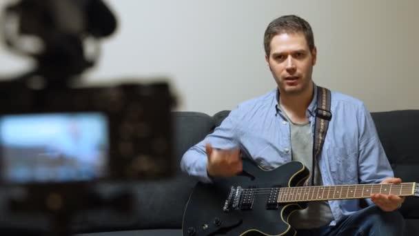 Muž s poloakustickou kytarou před videokamerou.