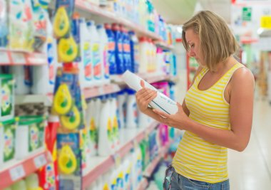 Woman choosing washing powder in grocery store.