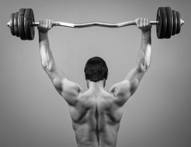 Muscular man doing exercises with barbell. Back view. Black and white.