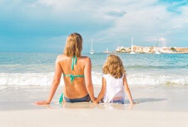 Woman and little girl sunbathing near the sea.