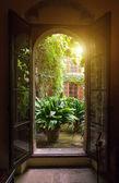 Pohled z otevřeného okna do zahrady