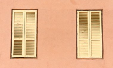 Two window with yellow shutters. Close-up view.