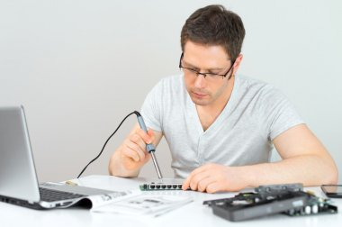 Male technician soldering lan switch router at his workplace.