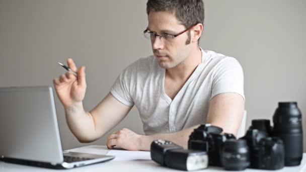 Fotograf wählt Fotos auf seinem Computer aus.