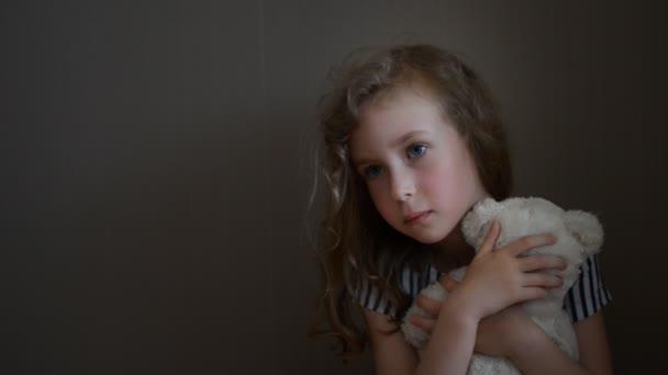 smutný holčička s medvědem u zdi