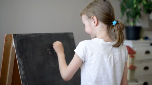 disegno faccia buffa sulla lavagna della bambina