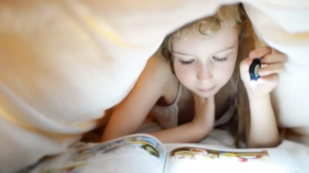 malá holčička čtení knihy pod peřinou