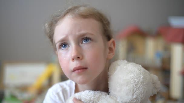 plačící holčička s medvědem v dětském pokoji.