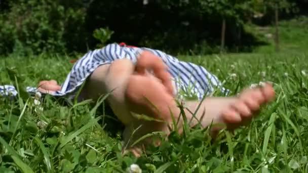 Little girl lying on green grass in the park.