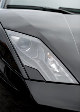 Close-up view of black sports car headlight.