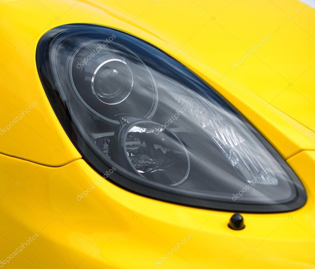 Close-up view of yellow sports car headlight.