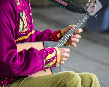 Man playing balalaika on the street. Unrecognizable person.