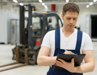 Handsome supervisor with tablet pc at the warehouse. Place for text.