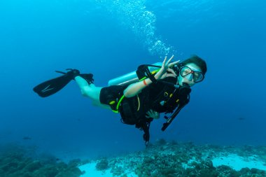 kadın dalgıç su altında gösterilen ok sinyal