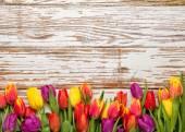 Fotografie fresh tulips arranged on old wooden background