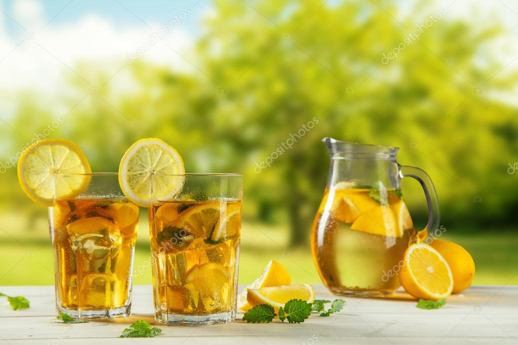 Cups of ice tea with trees on background