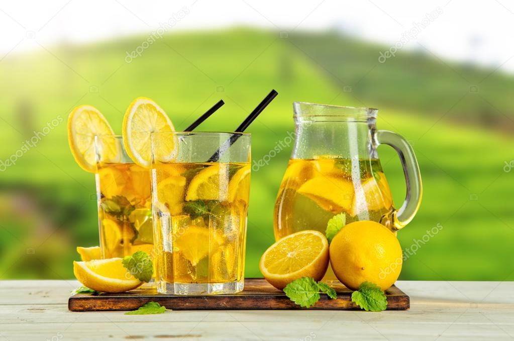 Cups of ice tea with plantation on background