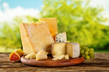 Various types of cheese placed on wooden table