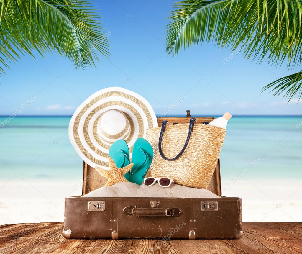 Old suitcase on tropical beach, travel concept