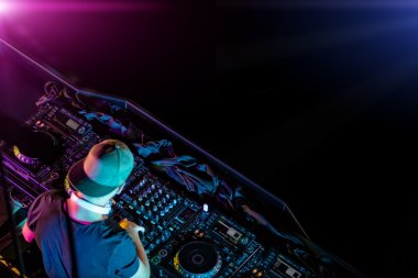 Disc jockey mixing electronic music in club