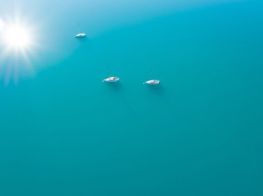 Aerial view of three yachts sailling on azure water