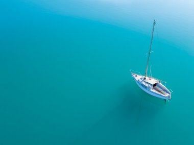 Aerial view of alone yacht sailling on azure water
