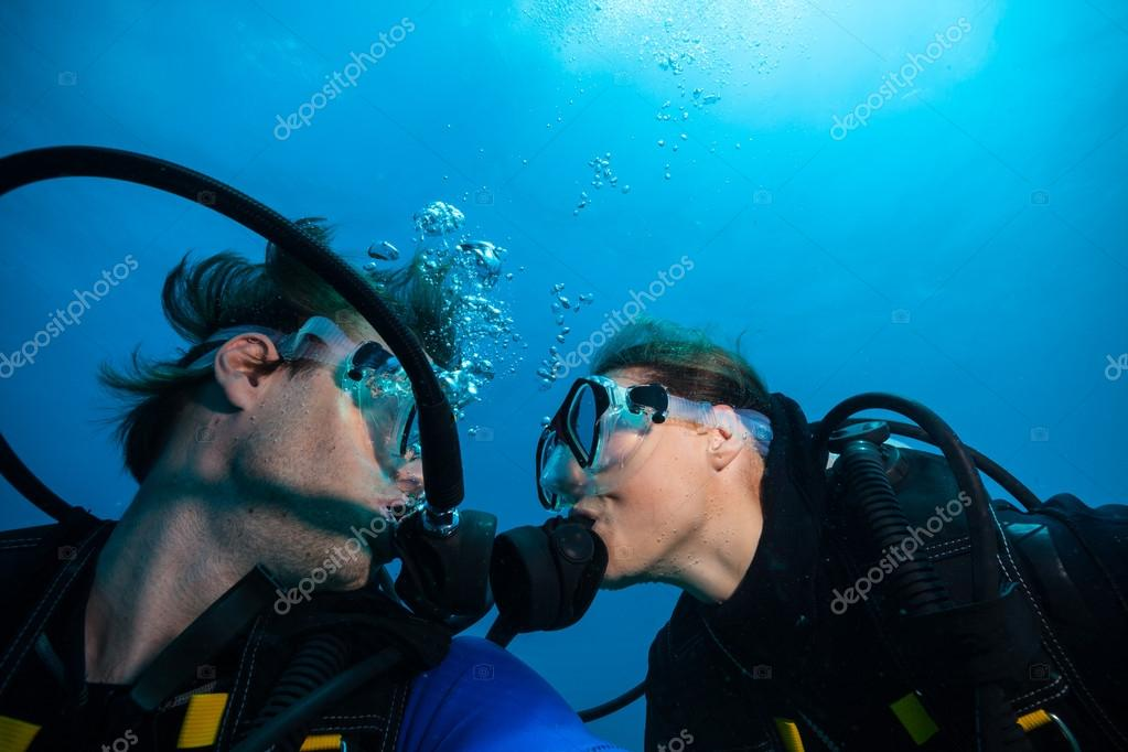 Scuba divers kissing each other underwater