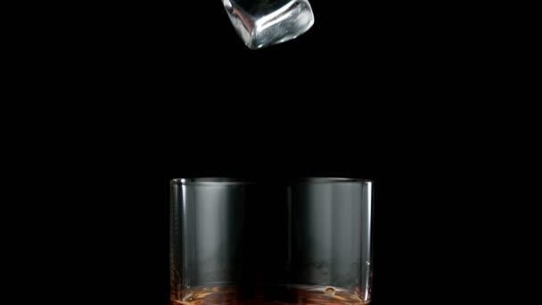 Super-Zeitlupe fallender Eiswürfel in Whiskey-Drink. Gefilmt mit High-Speed-Kinokamera, 1000 fps.