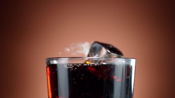 Super-Zeitlupe fallender Eiswürfel in Cola-Drink, Kamerafahrt. Gefilmt mit High-Speed-Kinokamera, 1000 fps
