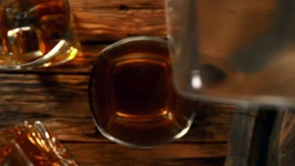 Super-Zeitlupe fallender Eiswürfel in Whiskey oder Rum mit Kamerafahrt. Gefilmt mit High-Speed-Kinokamera, 1000 fps.