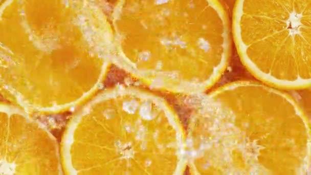 Super slow motion of orange slices with splashing water, top view. Filmed on high speed cinema camera, 1000 fps.