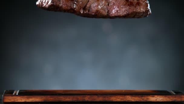 Létající kus grilovaného hovězího steaku padající na stůl. Natočeno na vysokorychlostní kameře, 1000 fps.