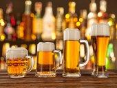 Fotografie Glasses of light beer with bar on background