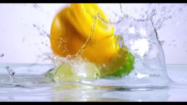 Orange and lime splashing in slow motion